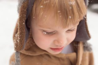 Image of child toddler boy with snowflakes on his lashes and nose burlington family photographer